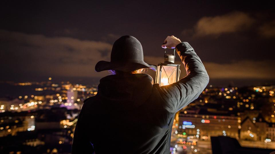 """Marco Carrara, a replacement watchman, holds a lantern as he looks out from the Lausanne Cathedral bell tower in Lausanne, Switzerland. """"This is the watchman! The bell has tolled 10. The bell has tolled 10."""" On a cold night in December, Carrara, who takes on the job on the permanent watchman's days off, repeats the message hourly, only changing the number of chimes that have rung. (Fabrice Coffrini / AFP)"""