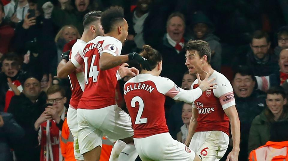 Arsenal's French defender Laurent Koscielny (R) celebrates with teammates after scoring a goal.
