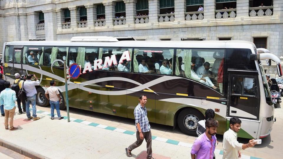 The file photo shows Congress MLAs, sitting in a bus, leaving the Vidhana Soudha after staging a protest dharna against the swearing-in of B S Yeddyurappa as Karnataka chief minister, in Bengaluru .