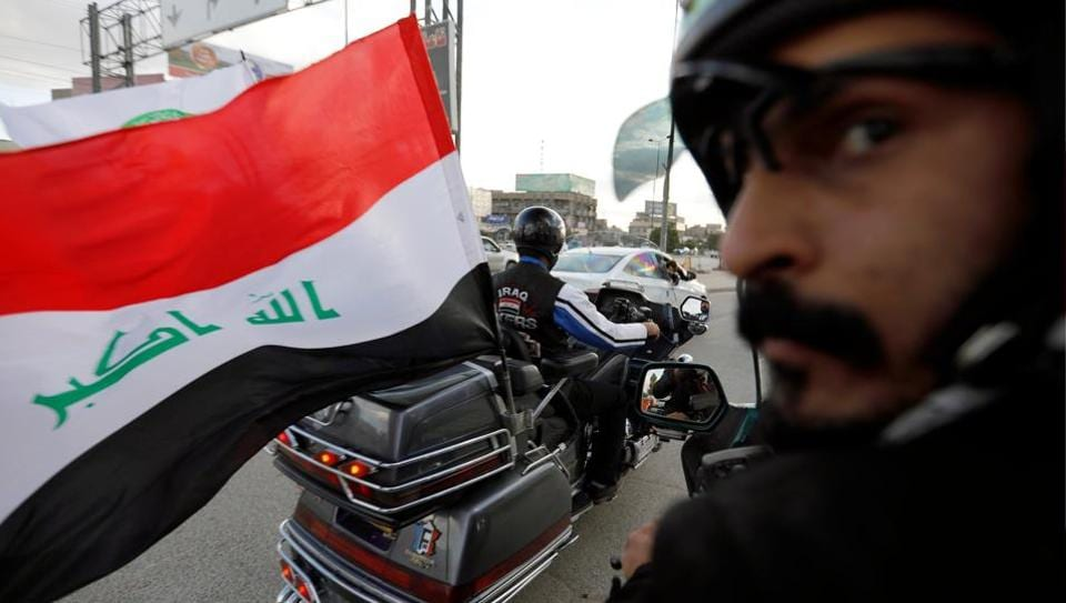 """A member of """"Iraq Bikers"""", the first biker group in the country, drives with an Iraqi flag in Baghdad. Roaring along Baghdad's highways, Iraq Bikers are doing more than showing off their love of outsized motorcycles and black leather: they want their shared enthusiasm to help heal Iraq's deep sectarian rifts. (Thaier Al-Sudani / REUTERS)"""