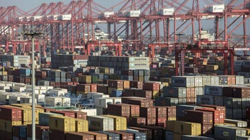 Containers sit stacked next to gantry cranes at the Yangshan Deep Water Port in Shanghai, China, July 10, 2018. China hopes to replace investment by mass consumption as its future growth engine.