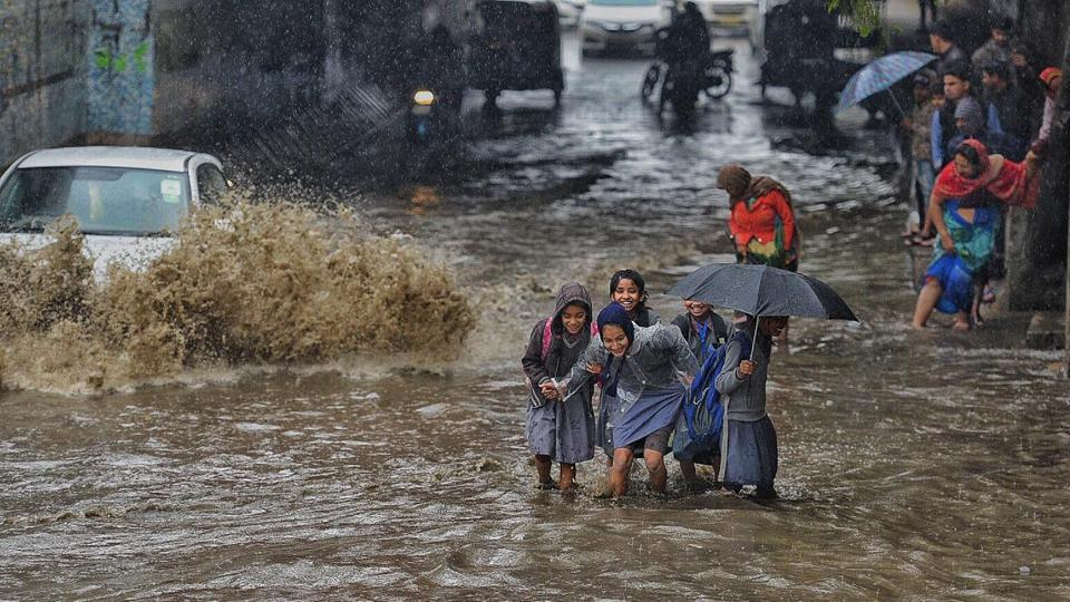 School students wade across a waterlogged road during heavy morning rain in east Delhi. Commuters were caught up in traffic jams in several places across Delhi as heavy rains and hailstorms hit the national capital and its neighbouring areas during rush hour on Tuesday morning. (Raj K Raj / HT Photo)