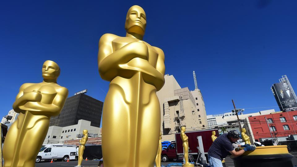 In this file photo taken on February 24, 2016 Rick Roberts works on touching up a base amid statues of the Oscar awaiting finishing up at a Hollywood back lot in Hollywood, California ahead this weekend's 88th Academy Awards.