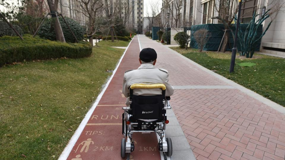 "A resident makes his way back to his apartment in an electric wheelchair. ""The idea that children should take care of their ageing parents is an old logic spanning thousands of years,"" explained Li. ""As society develops, this is changing."" (Greg Baker / AFP)"