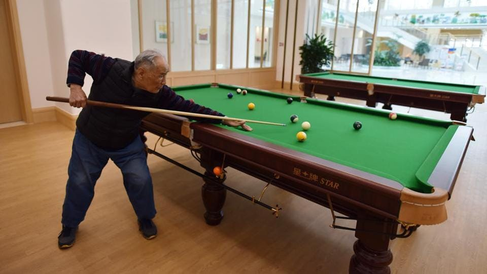 A resident plays pool in a recreation area at the Yanyuan community. The push to grow China's elderly care capacity has encouraged more private companies, from real estate developers to insurance firms, to seize on business opportunities in the industry, such as nursing homes where residents enjoy five-star accommodations and professional medical support. (Greg Baker / AFP)
