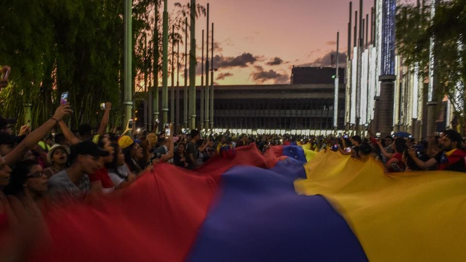 "Venezuelans hold a demonstration in Medellin, Colombia in support of Juan Guaido. Analysts at the Eurasia Group consultancy noted that while international recognition of Guaido cemented his position as the main opposition leader, he had failed to win over senior elements of the military. In that light, ""Maduro's fall does not appear imminent,"" the analysts wrote. (Joaquin Sarimento / AFP)"