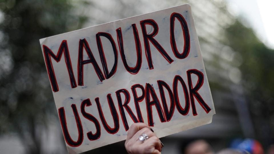 "A woman holds a sign reading ""Maduro usurper"" as she gathers in support of Juan Guaido outside the Embassy of Venezuela in Mexico City. US President Donald Trump immediately issued a statement recognising Guaido as Venezuela's interim president. Brazil, Canada, Chile, Colombia, Peru and several countries in the region also gave their backing. The European Union called for free elections to restore democracy. (Edgard Garrido / REUTERS)"