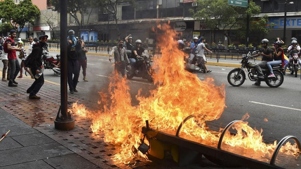 A protester burns a motorcycle during clashes with the security forces. Maduro's reelection last year was contested by the opposition, and criticised internationally -- but the socialist leader has until now retained the loyalty of the powerful military, whose response was being keenly watched. (Yuri Cortez / AFP)