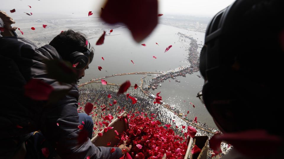 Uttar Pradesh government officials throw rose petals from a helicopter during Kumbh Mela in Prayagraj, Uttar Pradesh. (Prayagraj Mela Authority Handout / AFP)