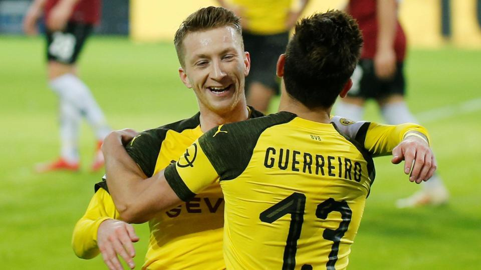 Borussia Dortmund's Raphael Guerreiro celebrates scoring their fourth goal with Marco Reus.