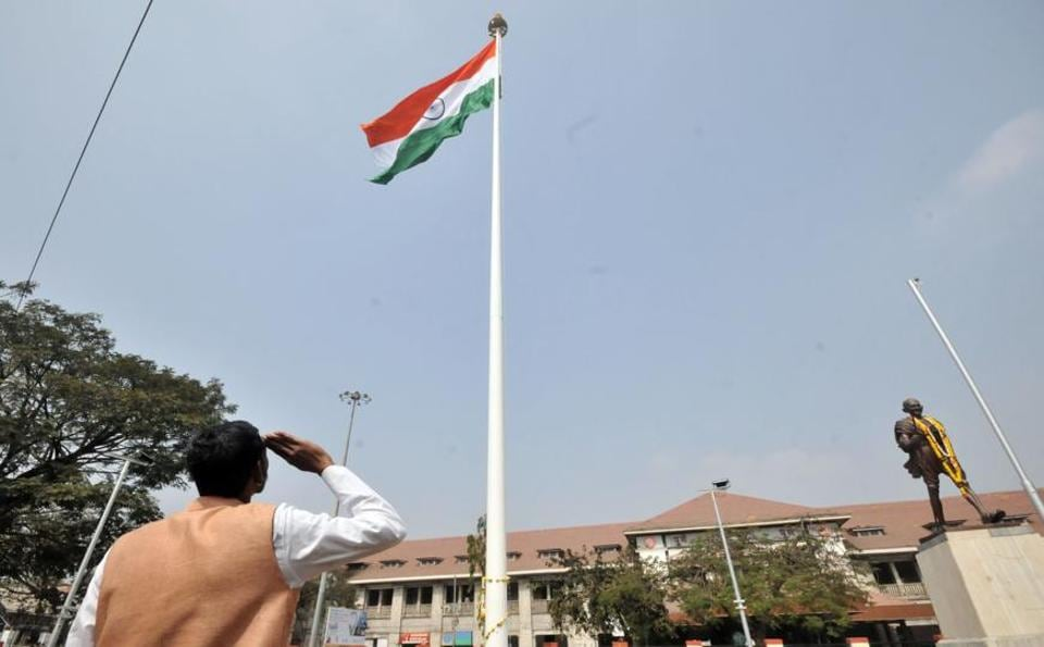 A man salutes the Indian flag hoisted on the 100ft flag pole at Pune railway station on Republic Day. (HT PHOTO)