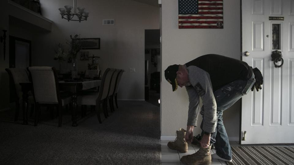 "Chris George takes off his boots at his home after spending the day working as a handyman. ""My rebuttal to the president every time he puts out a tweet is to flash my GoFundMe account. That's my rebuttal to his comments that are absolutely outrageous,"" George said. ""Here we are being pawns for an agenda of a wall."" (Jae C. Hong / AP)"