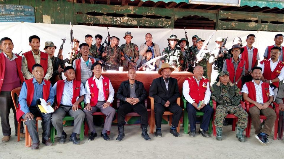 Khango Konyak (in suit and hat) with Isak Sumi (to his left, in a black jacket) and members of the civil society pose with members of the Konyak faction of NSCNK).