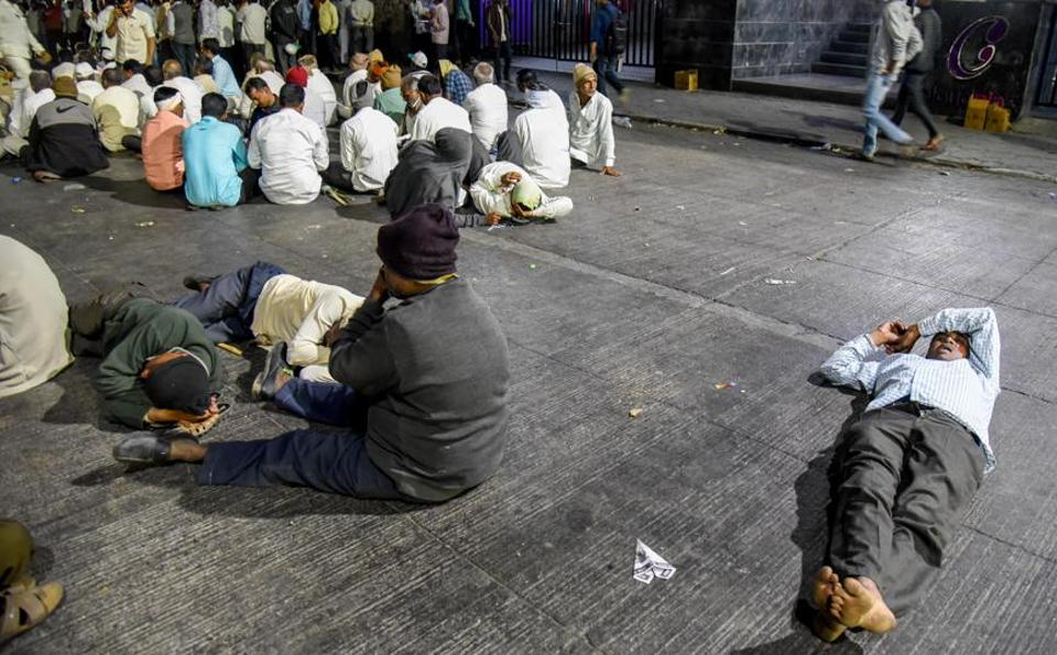 Members of Swabhimani Shetkari Sanghatana sit outside Sakhar Sankul as they wait for their demands to be fulfilled in Pune