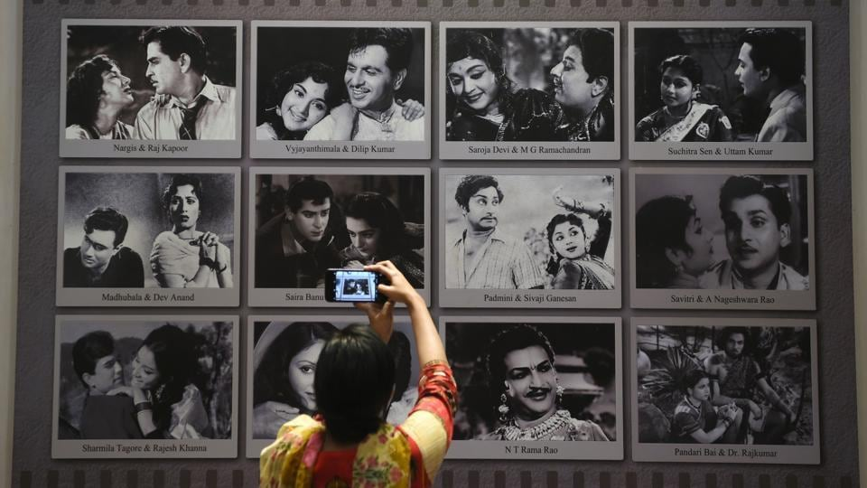 """A visitor takes a picture of a display with images of former Indian movie actors at the National Museum of Indian Cinema (NMIC), the country's first museum showcasing the history of its film industry, in Mumbai. """"It showcases to the world outside what Indian cinema has achieved in its entirety over more than 100 years,"""" Amrit Gangar, a consulting curator on the project, told AFP. (Punit Paranjpe / AFP)"""