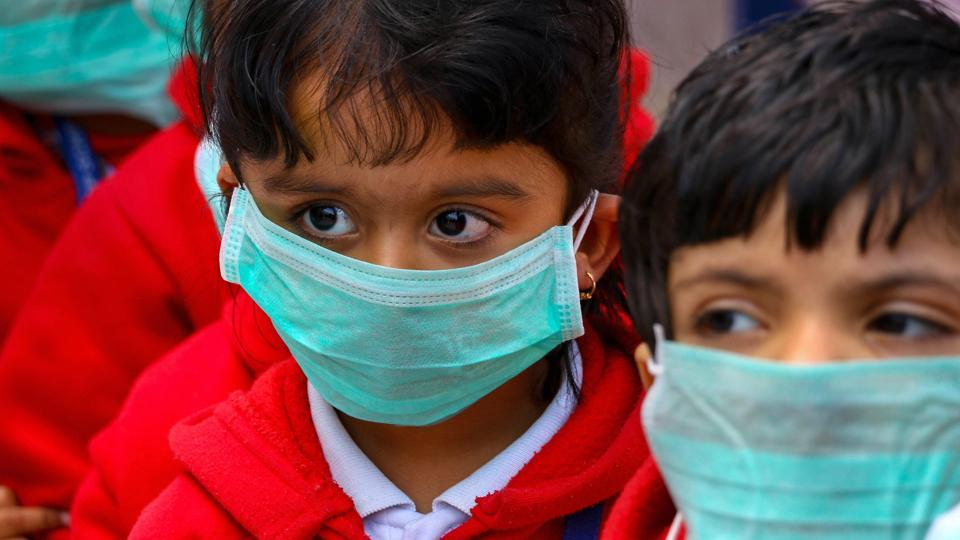 Students, wearing masks as protection against swine flu, attend school in Ajmer, Rajasthan on Wednesday.