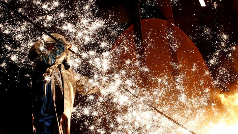 A steel worker of Germany's industrial conglomerate ThyssenKrupp AG, stands amidst emitting sparks of raw iron from a blast furnace at Germany's largest steel factory in Duisburg. (Wolfgang Rattay / REUTERS)