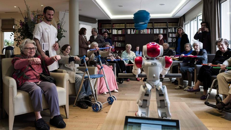 Elderly people take part in activities led by a humanoid robot named Zora during a presentation to the press on the occasion of the nationwide launch of the service at a Maisons de Famille retirement home (EPHAD) in Paris, France. (Philippe Lopez / AFP)