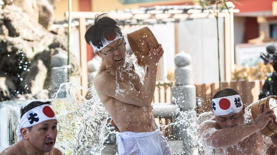 "Shinto followers pour cold water over themselves to purify body and soul as part of an endurance ritual at Kanda Shrine, known as ""Kanda Myojin"", in Tokyo, Japan. (Martin Bureau / AFP)"