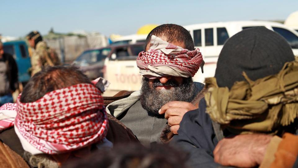 Alleged Islamic State (IS) group fighters who fled from the frontline Syrian village of Baghuz, near the Iraqi border, sit blindfolded in the back of a pickup truck after being taken into custody by SDF forces for screening, near the Omar oil field in the countryside of the eastern Syrian Deir Ezzor province. (Delil Souleiman / AFP)