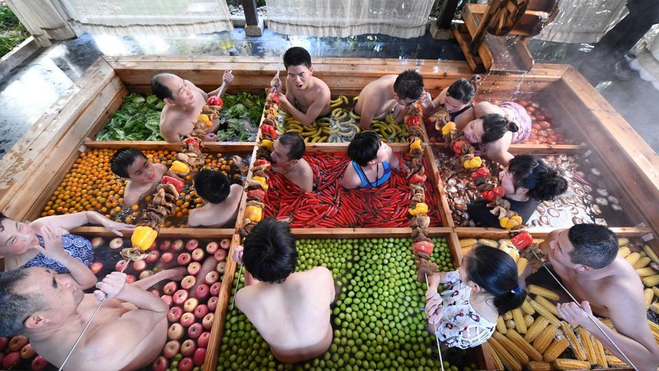 People enjoy a barbecue as they bath in a hotpot-shaped hot spring filled with fruits and vegetables, at hotel in Hangzhou, Zhejiang province, China. (REUTERS)