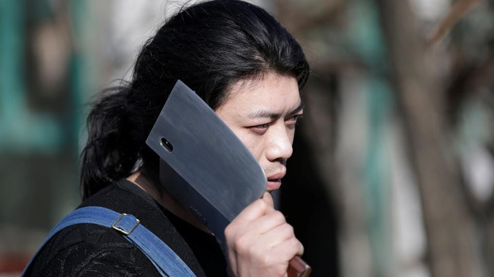 Geng Shuai, poses with an invention, a mobile phone case in the shape of a cleaver, outside his workshop. Geng's creative mind is a joy to watch, said Zhou Bingke, who teaches welding and metalwork at Tsinghua University. (Jason Lee / REUTERS)
