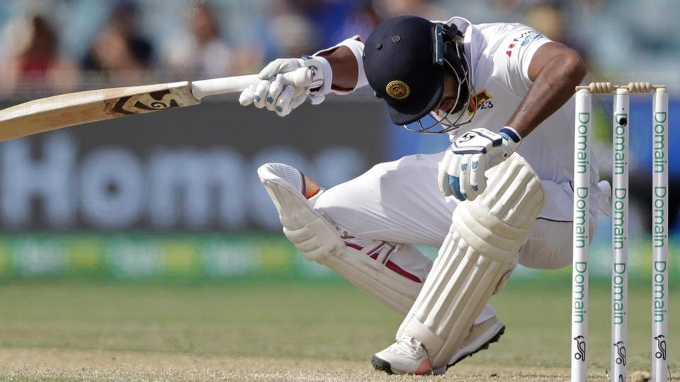 Dimuth Karunaratne falls to the ground after he was struck in the head by a delivery from Australia's Pat Cummins.