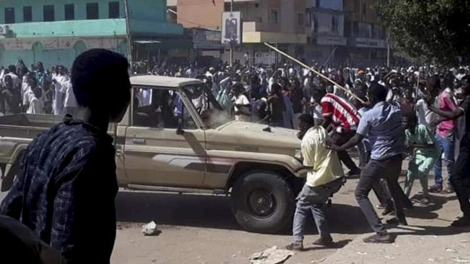 In this, Dec. 23, 2018 handout photo provided a Sudanese activist, people chant slogans and attack a national security vehicle during a protest, in Kordofan, Sudan. The protest on Sunday was the latest in a series of anti-government protests across Sudan, initially sparked by rising prices and shortages.