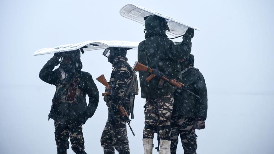 Indian paramilitary personnel stand guard on the shore of the Dal lake during heavy snowfall in Srinagar, Jammu and Kashmir. (Tauseef Mustafa / AFP)