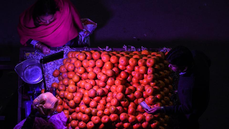 A woman purchases oranges from a roadside vendor in New Delhi. (Sajjad Hussain / AFP)