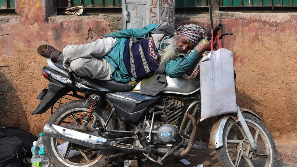 A man sleeps on a motorbike in the old quarters of Delhi. (Sajjad Hussaiin / AFP)