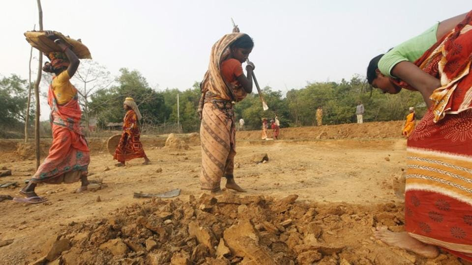 Village women work at a road construction site under the National Rural Employment Guarantee Act (NREGA), an anti-poverty plan that provides 100 days of employment every year to tens of millions of rural poor, in East Midnapore district, West Bengal.