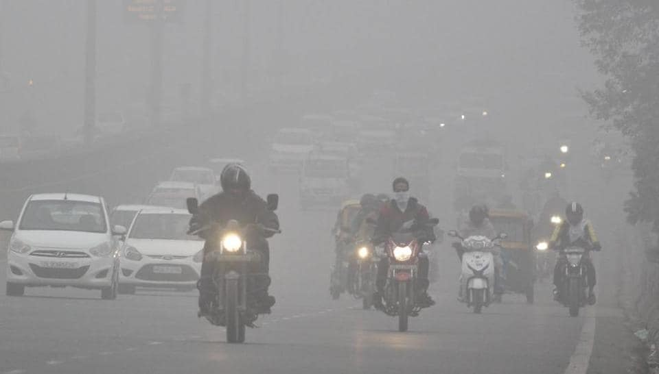 Commuters make their way through fog on a cold winter day, at Delhi-Gurugram Expressway, in Gurugram, India.