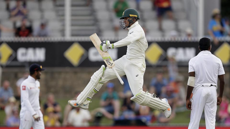 Australia's Usman Khawaja jumps up as he celebrates making 100 runs against Sri Lanka on day 3 of their cricket test match in Canberra, Sunday, Feb. 3, 2019
