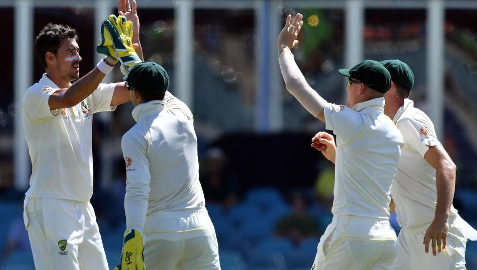 Australia's Mitchell Starc celebrates his wicket off Sri Lanka's batsman Dinesh Chandimal with a teammates during day four of the second Test cricket match between Australia and Sri Lanka at the Manuka Oval Cricket Ground in Canberra on February 4, 2019.