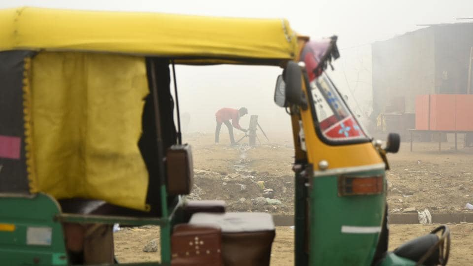 A youth washes his hands using water from a hand pump next to a parked auto rickshaw in the morning fog in Greater Noida, Uttar Pradesh. (R S Iyer / AP)