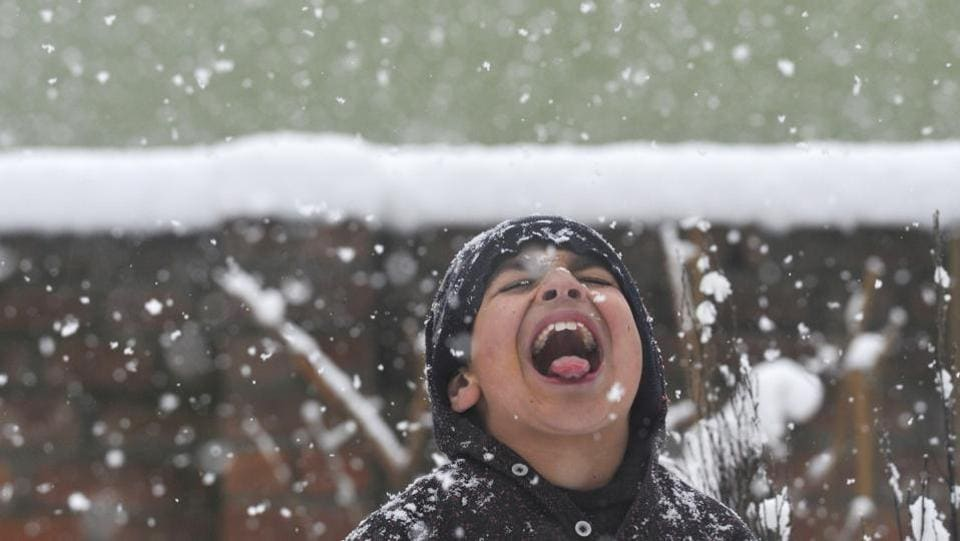A boy tries to catch snowflakes during fresh snowfall in Srinagar, Jammu and Kashmir. (Waseem Andrabi / HT Photo)