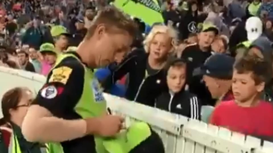 Daniel Sams signs on his cap for a young fan.