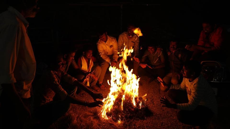 People sit around camp fire on a winter evening at Gujarwadi in Pune, India, on Saturday.