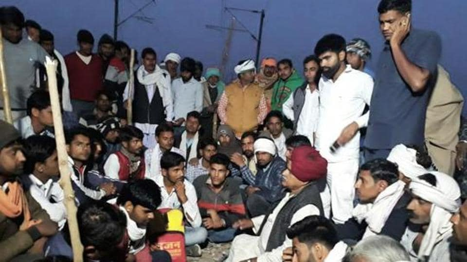 K S Bainsla along with Gujjar supporters sit on tracks at Malarna railway station to block railway route in Sawai Madhopur on Friday.