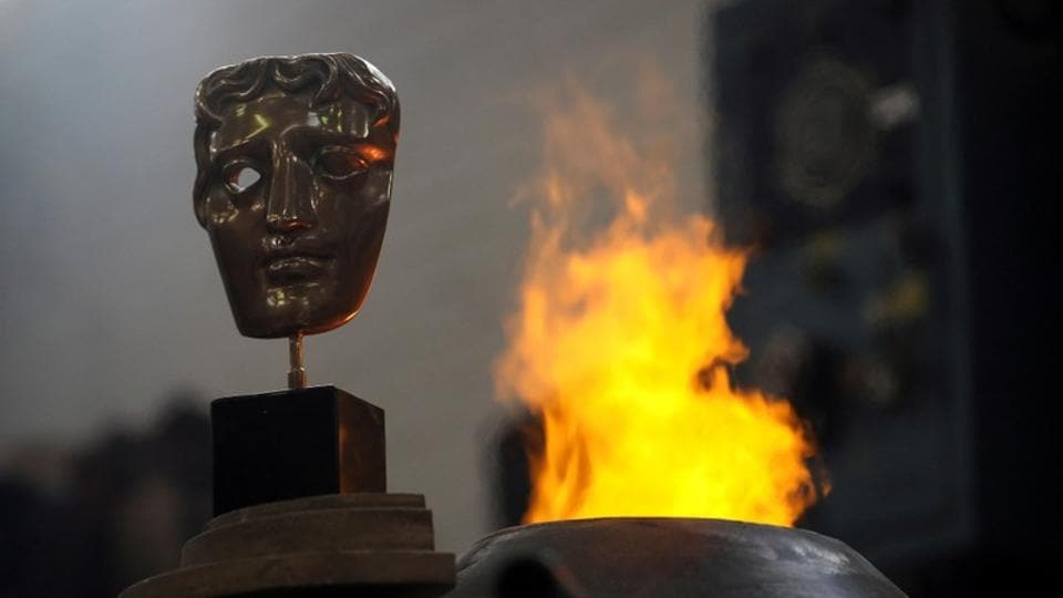 A completed British Academy of Film and Television Awards (BAFTA) mask is placed next to a furnace to be photographed at a foundry in west London.