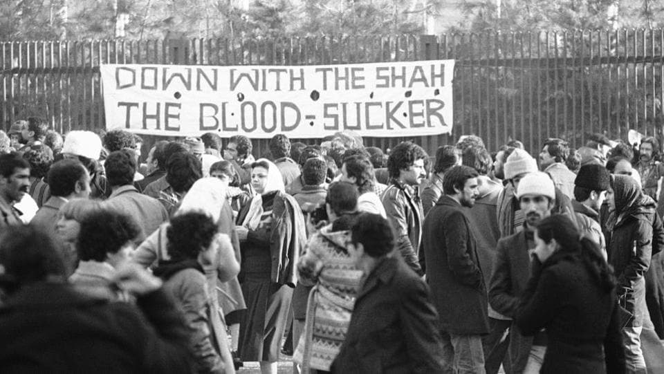 A banner denouncing the shah at the entrance of Tehran University in January 1979. In December, rioters burned down the headquarters of the US Grumman Aircraft Corp in Isfahan. An attempt to storm the US Embassy in Tehran resulted in US Marines firing tear gas. On December 29, the shah asked Shapour Bakhtiar of the opposition National Front to form a civilian government. (Bernhard Frye / AP File)