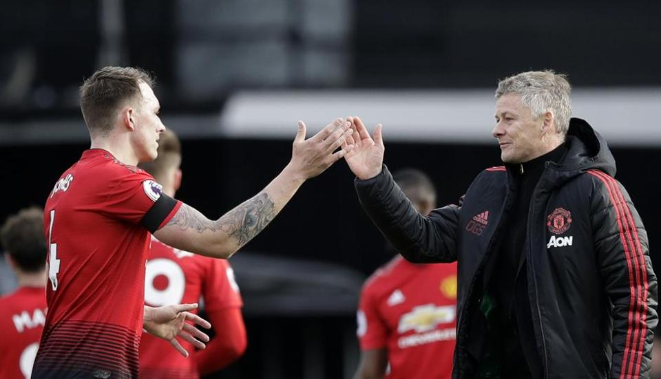 Manchester United caretaker head coach Ole Gunnar Solskjaer, right, and Manchester United's Phil Jones celebrate at the end of the English Premier League soccer match between Fulham and Manchester United