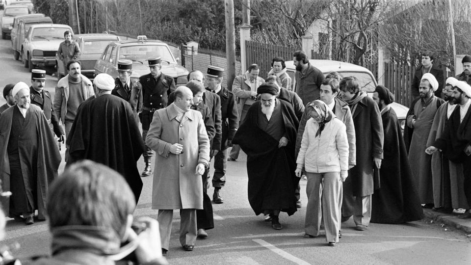"Future Iranian President Hassan Rohani (background 2nd-R, with turban and glasses) among companions of Ayatollah Ruhollah Khomeini walking out of his villa in France. On January 13, the shah appointed a regency council to represent the crown during his absence, while the Ayatollah announced the formation of a revolutionary council to prepare for an ""Islamic republic"" from Paris. (Marcel Binh / AFP File)"
