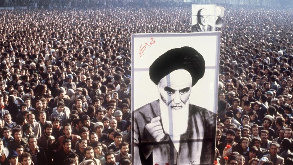 "Demonstrators hold a poster of Ayatollah Ruhollah Khomeini on January 01, 1979, during a demonstration in Tehran. The same day Shah Mohammad Reza Pahlavi appeared before reporters for the first time in two months and conceded that he ""would love"" to go on a vacation ""in the situation permits."" (AFP File)"
