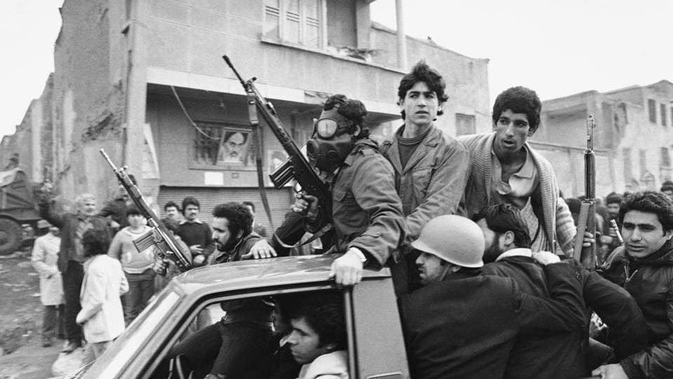 Armed rebels, one wearing a gas mask, ride in a truck near the headquarters of Ayatollah Khomeini in Tehran. Imperial guards were sent in to quell a pro-Khomeini demonstration by air force cadets in Farahabad on February 09. Islamists and leftist guerrillas fought imperial troops around the base the next day resulting in the troops' retreat with heavy losses. (Campion / AP File)