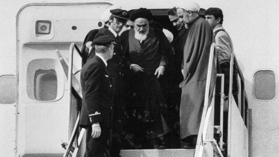 Ayatollah Ruhollah Khomeini emerges from a chartered Air France, accompanied by supporters and 120 international journalists as a measure against threats, upon his arrival at Mehrabad airport in Tehran, Iran on February 01, 1979. (FY / AP File)