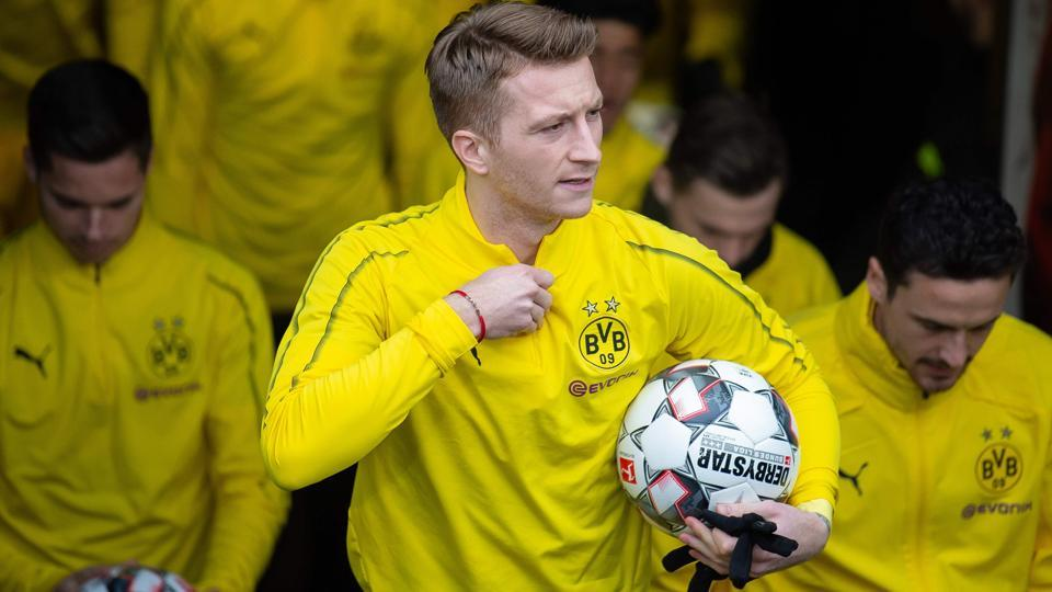 Marco Reus carries the ball as he and his teammates come out to warm up.