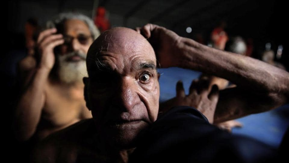 Hindu men get their hair cut in a ritual before becoming Naga Sadhus at Sangam, the confluence of three holy rivers during the Kumbh Mela. At every Kumbh, including this year's, thousands of devotees are initiated into the reclusive sect of the Naga Sadhus — naked, ash-smeared cannabis-smoking Hindu ascetics and onetime-armed defenders of the faith who for centuries have lived in jungles and caves. (Rajesh Kumar Singh / AP)