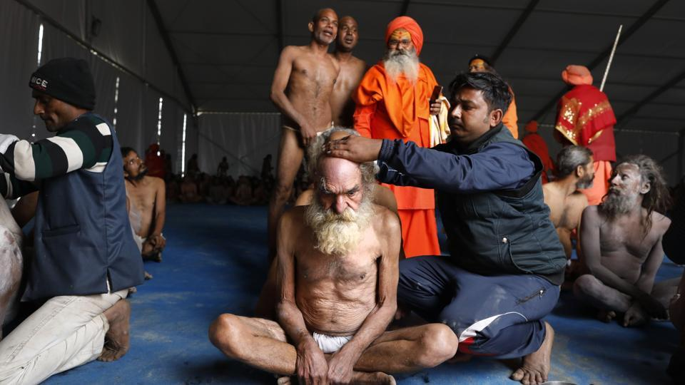 Performed by senior priests, the elaborate process of initiation comprises five rituals, starting with the shaving of heads and beards, ritual offering of saffron robes, wearing prayer beads, applying ash on the body and giving up their last piece of clothing. (Rajesh Kumar Singh / AP)